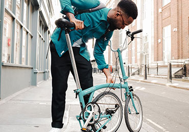 Man folding down a Brompton B75 bike thumbnail