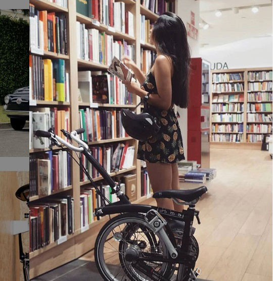 Woman in a bookshop browsing for books with a Brompton folding bike