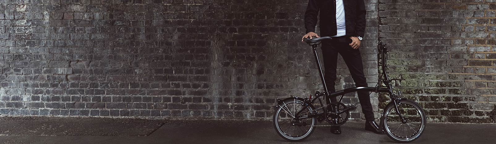 Man with a Brompton Black Edition against a charcoal brick wall, Brompton Italia